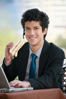 Businessman eating sandwich while using laptop