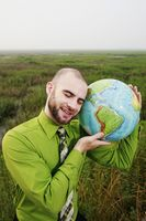 Businessman holding a globe near his face with his eyes closed