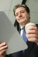 Businessman holding clipboard and a cup of coffee