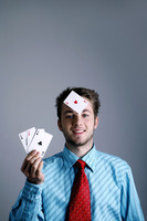 Businessman holding three playing cards with another one on his forehead