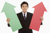 Businessman holding up a red and green arrow