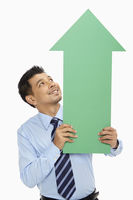 Businessman holding up an arrow, pointing upwards