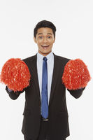 Businessman holding up red pom poms