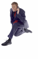 Businessman jumping while talking on the hand phone