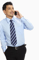 Businessman leaning against a wall, talking on mobile phone