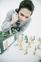 Businessman looking at his toy soldiers while talking on the phone