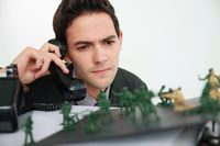 Businessman looking at toy soldiers while talking on the phone