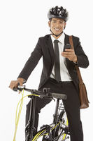 Businessman on bicycle reading text message