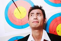 Businessman on target with arrow next to him