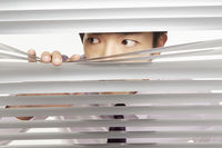 Businessman peeking through window blinds