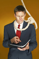 Businessman reading a document with a rope hanging around his neck