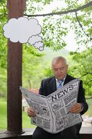 Businessman reading newspaper with thinking bubble above him