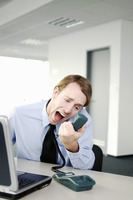 Businessman screaming into the phone receiver