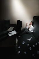 Businessman sitting and crying, crumpled papers scattered on the floor