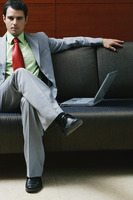 Businessman sitting on the couch with a laptop beside him