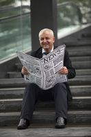 Businessman sitting on the stairs reading newspaper