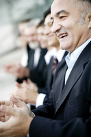 Businessman smiling while clapping hands