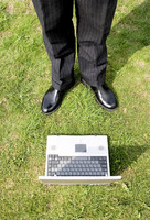 Businessman standing with laptop on the field