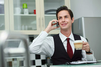 Businessman talking on the phone while drinking coffee