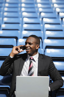 Businessman talking on the phone while using laptop in stadium