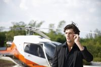 Businessman talking on the phone with helicopter in the background