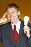 Businessman thinking while holding a light bulb