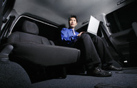 Businessman using laptop in the car