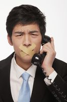 Businessman with his mouth taped, trying to talk on the telephone
