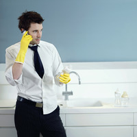 Businessman with rubber gloves holding milk bottle while talking on the phone