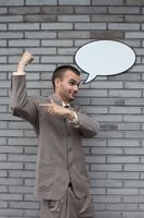 Businessman with speech bubble showing off his arm muscle