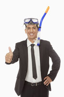 Businessman with swimming gear giving thumbs up