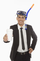 Businessman with swimming gear holding a disposable cup