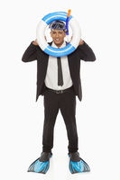 Businessman with swimming gear looking through a swimming tube