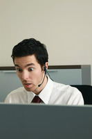 Businessman with telephone headset looking shocked