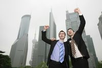 Businessmen cheering with arms raised
