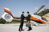 Businessmen shaking hands by helicopter