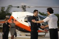 Businessmen shaking hands while businesswomen are walking from helicopter in the background