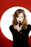 Businesswoman aiming a pistol at the camera
