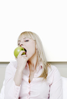 Businesswoman biting a green apple