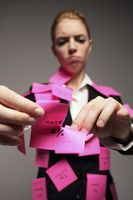 Businesswoman covered with adhesive notes tearing up messages on paper