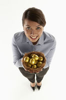 Businesswoman holding a nest filled with golden eggs