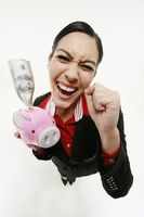 Businesswoman holding piggy bank with money