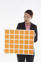 Businesswoman holding up a board of adhesive notes
