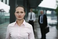 Businesswoman in formal clothing, businessmen in the background