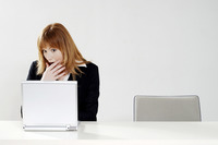 Businesswoman in shock while using laptop