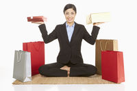 Businesswoman lifting gift boxes while sitting on the floor