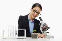 Businesswoman looking through a microscope