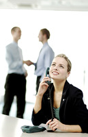 Businesswoman on the phone while businessmen shaking hands on the background