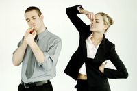 Businesswoman pinching her nose while businessman smoking
