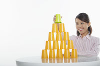 Businesswoman placing disposable cup on top of stack